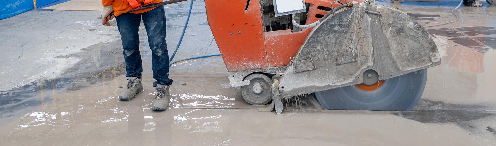 construction worker cutting concrete floor